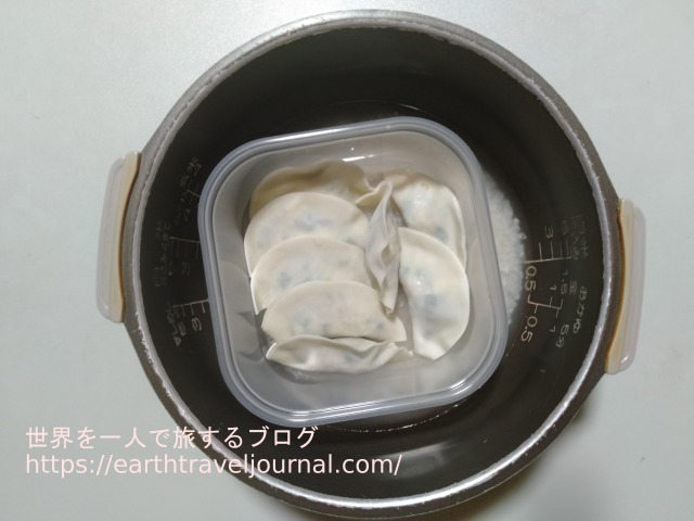 蒸し餃子コンテナ容器を炊飯器に置く